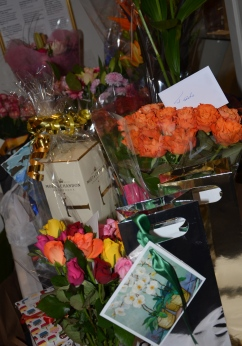 Ett stort berg med blommor och presenter.