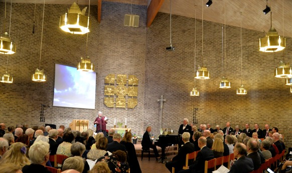 Minneskonsertens presentatör Monica Axelsson presenterar konsertens program och berättar om artisterna och vad de kommer att framföra.