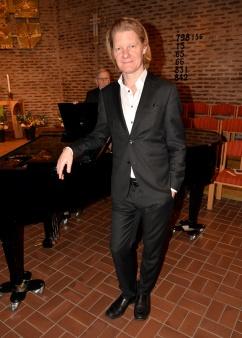 Mästerpianisten och kompositören Johan Ullén väntar på att få spela efter presentationen av Monica Axelsson.